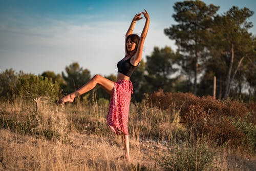 Tranquil barefoot woman in sports bra and skirt dancing with raised hands on hill in nature in sunlight