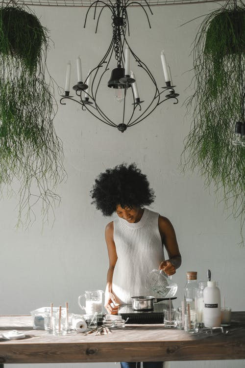 Ethnic craftswoman making candles in modern workshop