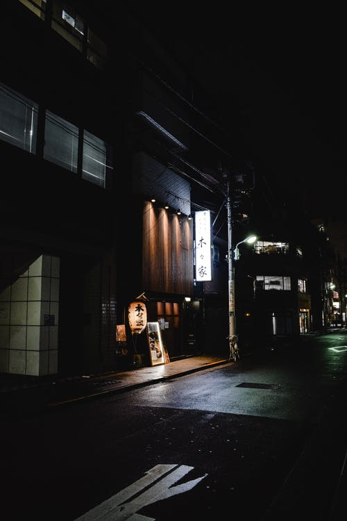 Woman in Black Jacket Standing in Front of Store during Night Time