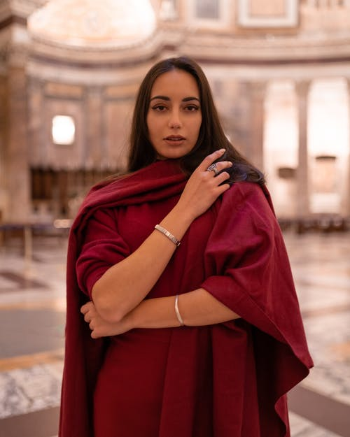 Charming young brunette in dark red loose dress raising arms in front and looking at camera while standing in grand majestic gallery