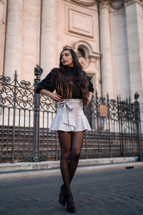 Stylish woman standing outside stone building