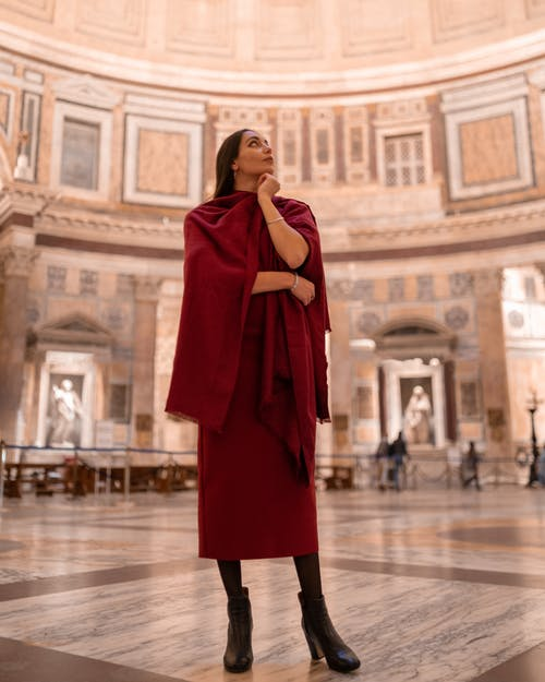 Full length elegant young brunette wearing dark red dress touching chin and looking up dreamily while standing in majestic gallery