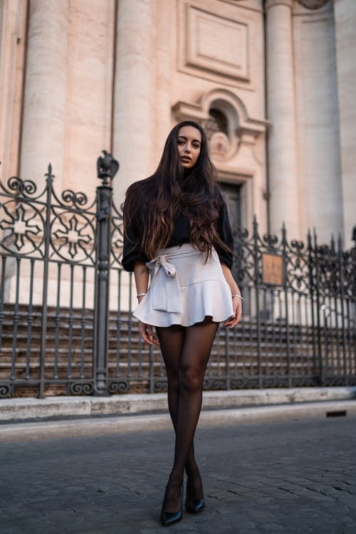 Stylish woman standing outside old stone building