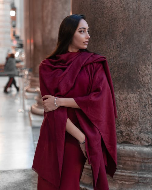 Serene young female wearing dark red fine clothes touching arm and looking away while standing near marble pillar outside majestic building