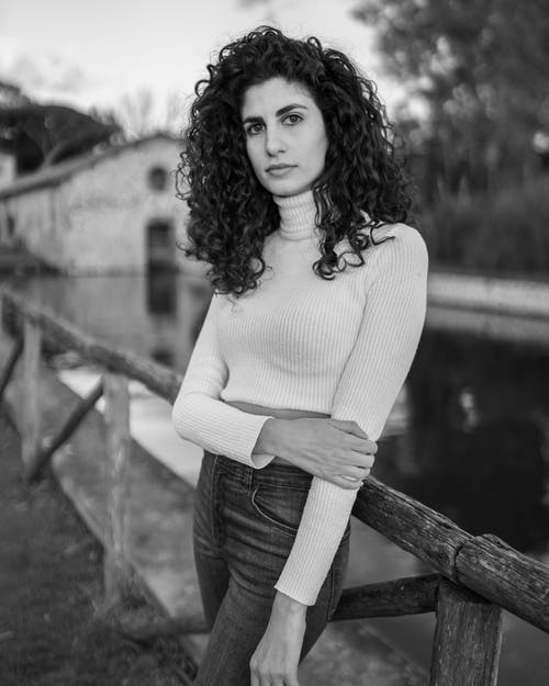 Black and white pretty young brunette with curly voluminous hair standing with one arm crossed near wooden fence on river shore in peaceful countryside