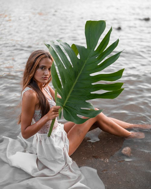 Gorgeous woman sitting on wet seashore with big green leaf