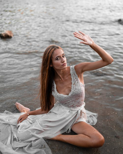 From above full body gorgeous young female wearing fancy maxi dress resting on wet seacoast with arm raised and looking at camera