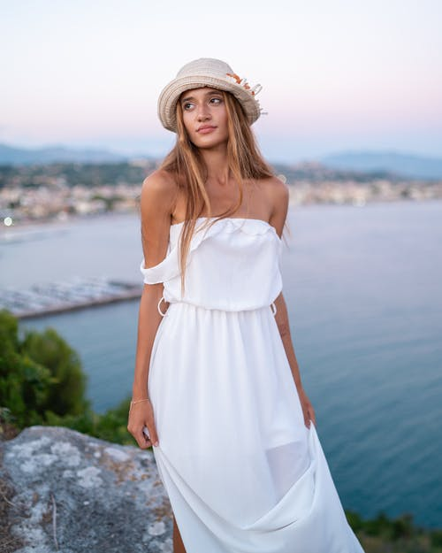 Charming woman in white dress standing on peaceful seashore