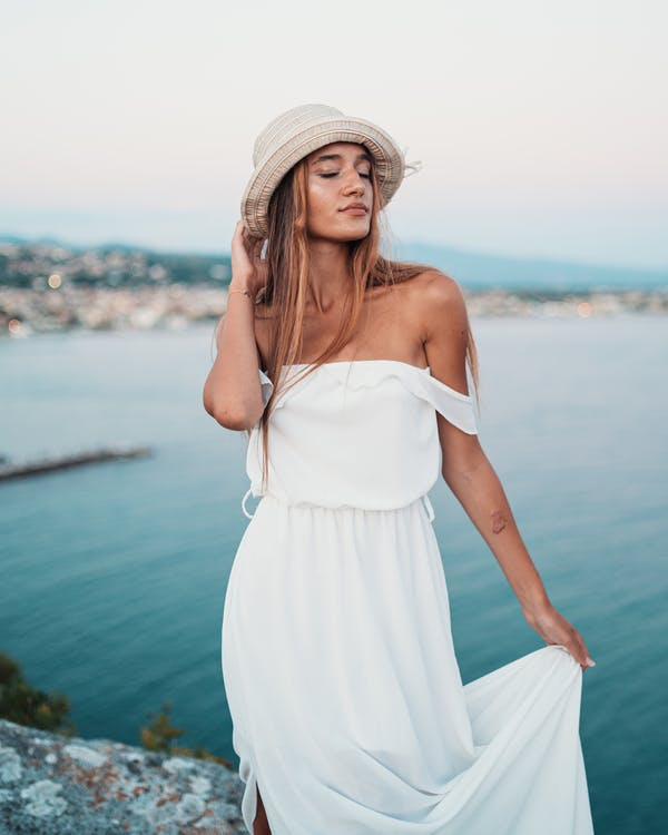 Stylish lady standing on cliff against ocean