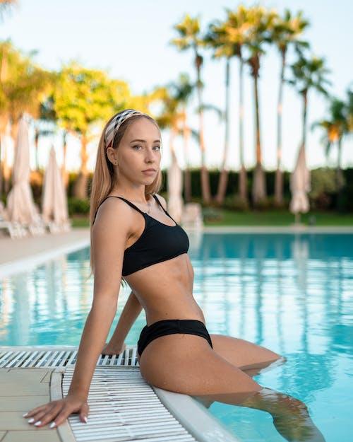 Charming female sitting on edge of poolside