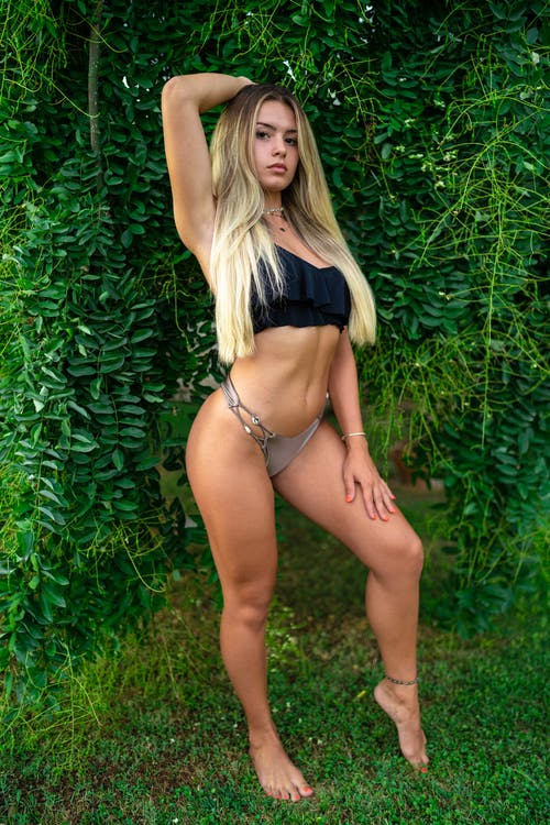 Full body of young female with long blond hair in bikini standing with raised arm against green plants and looking at camera in daytime