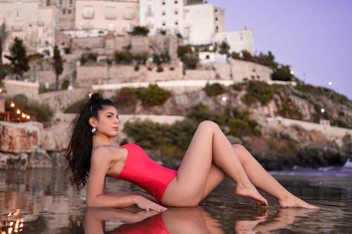 Slim woman lying on wet sand