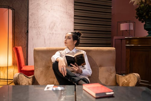 Confident woman with book on sofa