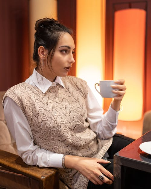 Thoughtful woman with cup of tea in cafe