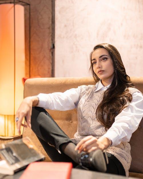 Stylish woman sitting on sofa at home