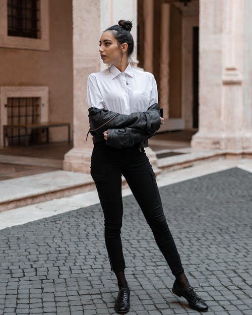 Slim woman standing on pavement near building
