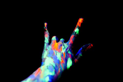 Faceless persons hand covered with neon paints showing shaka sign