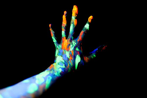 Crop unrecognizable persons hand with fingers spread covered with bright neon paints in dark studio