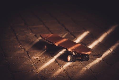 Brown Skateboard on Brown Concrete Floor
