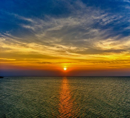 Scenic landscape with endless sea and bright sundown sky