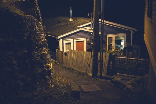 From above of small cozy wooden house illuminated by street lamp and located in countryside at night time