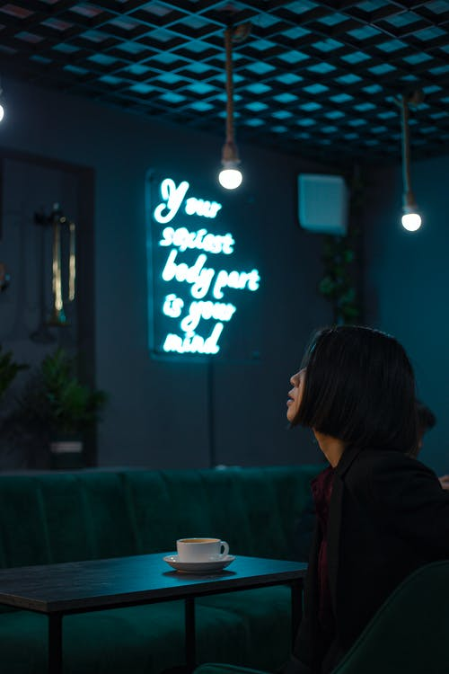Side view of serious young female sitting at table with cup of hot drink in cafe with bright luminous inscription on wall