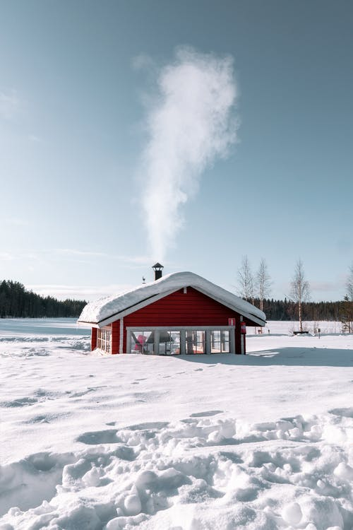 Lonely house covered with snow located in snowy terrain in sunny day in winter day