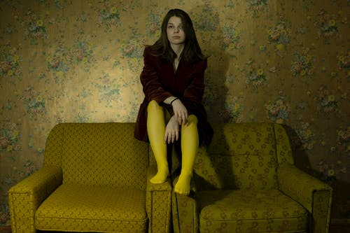 Stylish woman sitting on retro armchairs