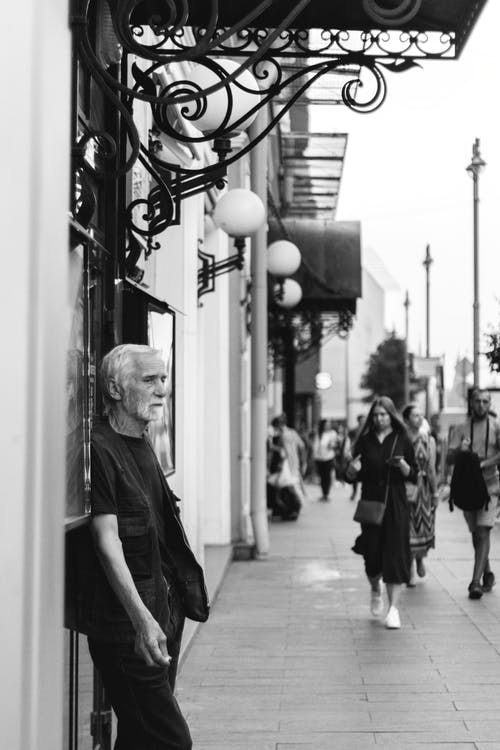 Black and white old man standing near wall and people walking along pavement of sidewalk in downtown