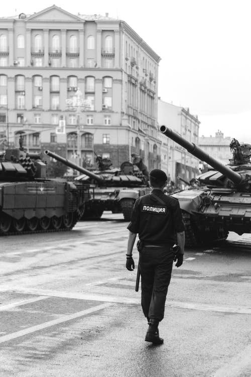 Policeman walking near tanks on city square
