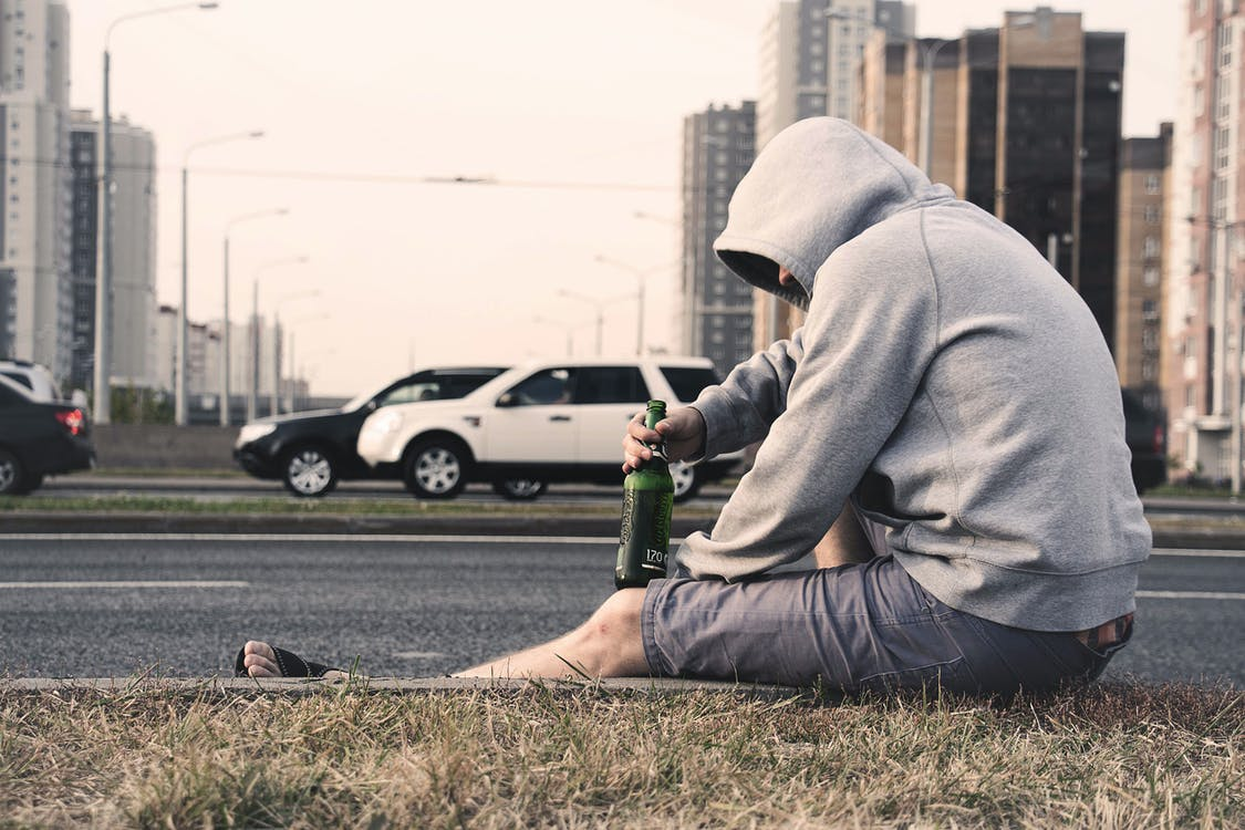 Person in Gray Hoodie Holding Beer