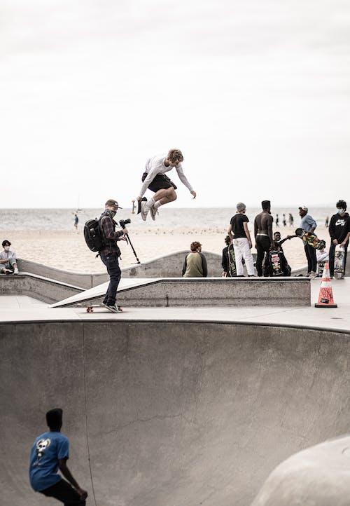 Man jumping on skateboard in skate park