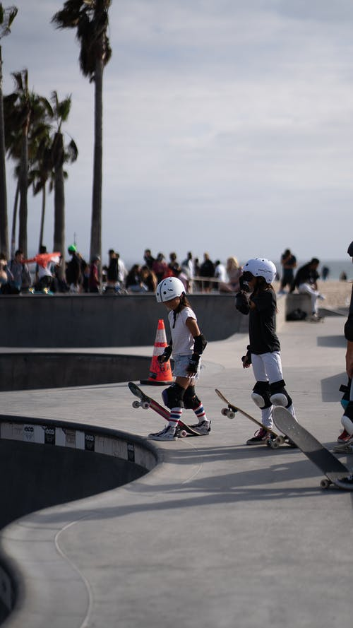 Anonymous kids with skateboards in skate park