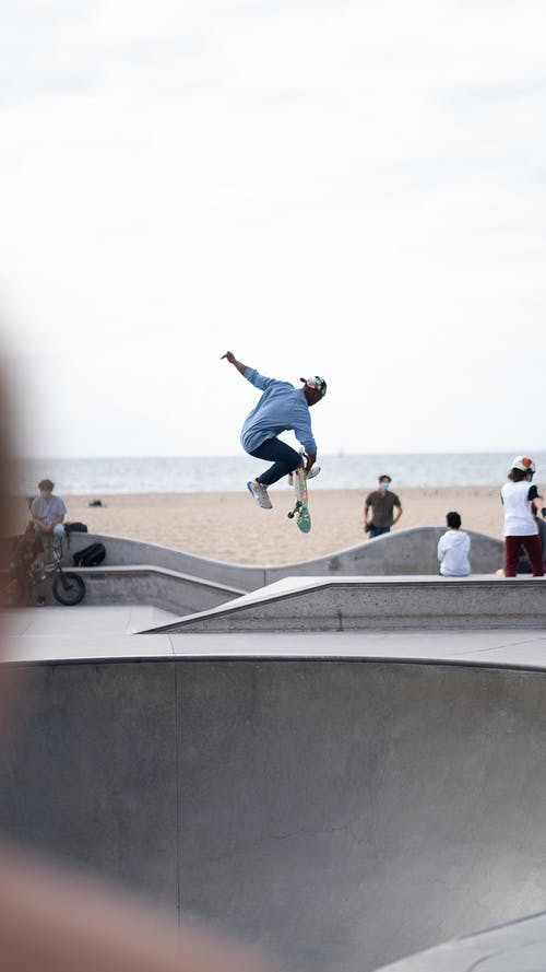 Unrecognizable ethnic male skater performing dangerous jump on skateboard in skater park near sea shore on cloudy day