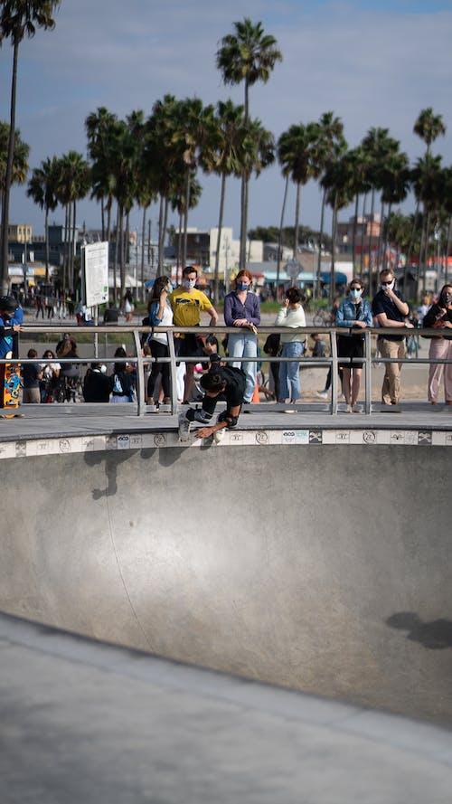 Unrecognizable young roller skater riding on ramp in skater park