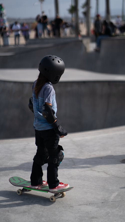 Anonymous kid wearing protection equipment while riding skateboard