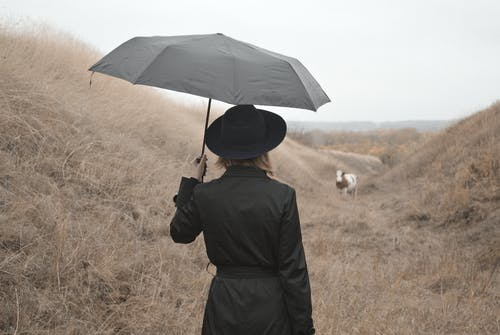 Woman with umbrella standing in countryside