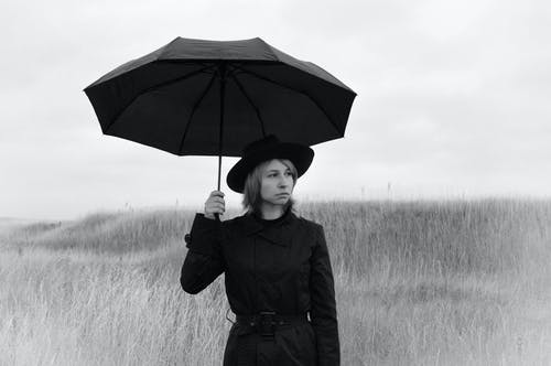 Black and white of serious pensive young female in coat and hat with umbrella looking away while standing on grassy field in gloomy rainy day