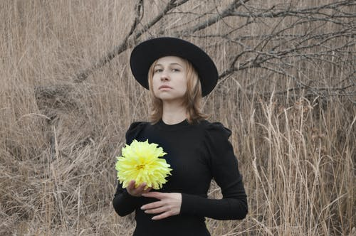 Tranquil elegant young female with blond hair in classic dress and hat standing near dry tree with flower in hand and looking at camera on gloomy autumn day