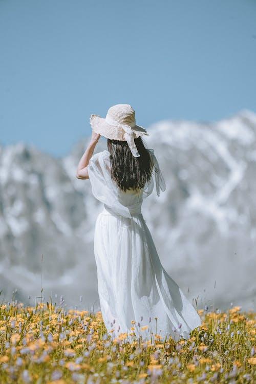 Woman in White Dress Standing on Yellow Flower Field