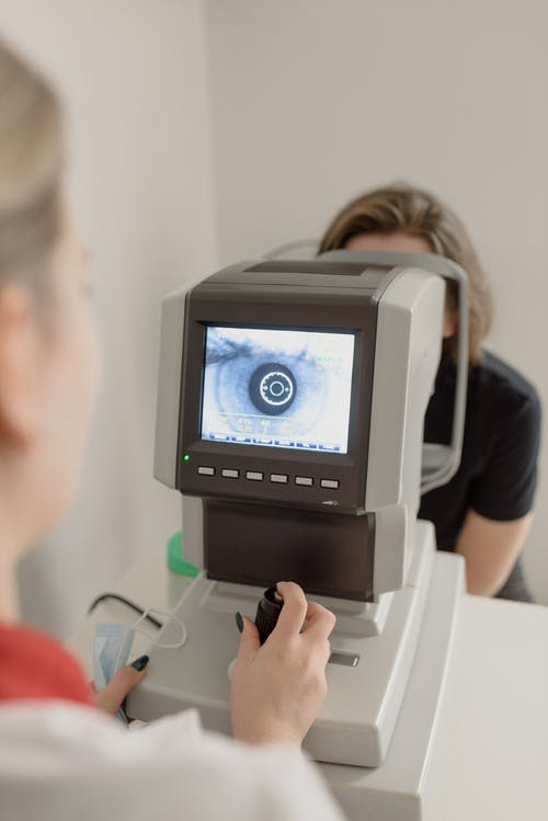 Unrecognizable ophthalmologist checking eyesight of woman on vision screener