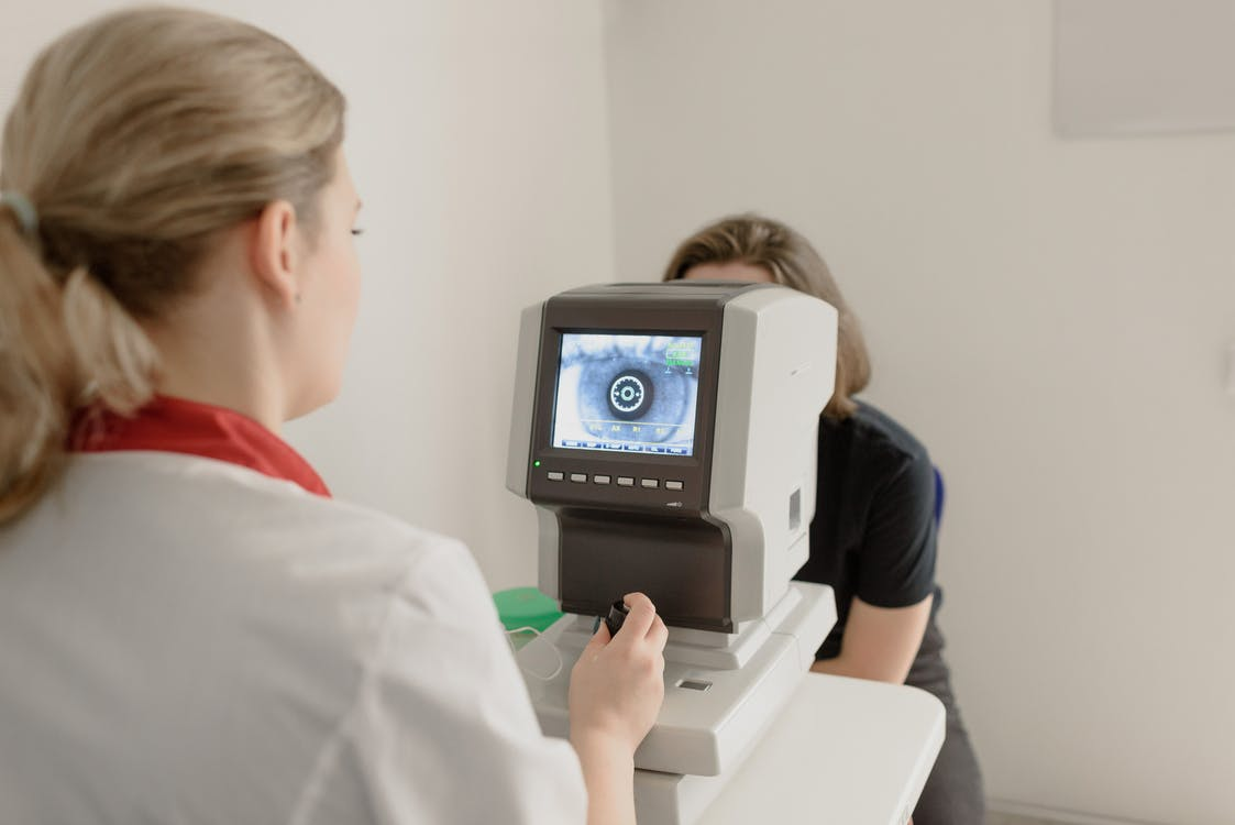 Anonymous oculist examining vision of patient on eye screener
