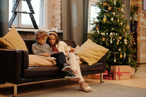 Two Kids Sitting on a Couch While Looking at a Digital Tablet