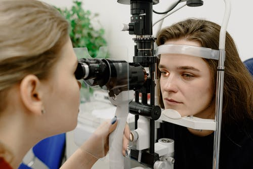Concentrated female medical specialist using professional tool for checking vision of patient in contemporary ophthalmology clinic