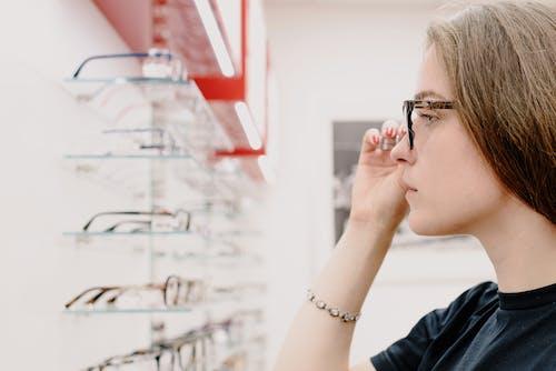 광학 저장소에 안경을 조정하는 젊은 여자