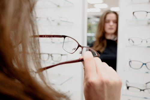 Back view of female client standing with rim while choosing eyeglasses in ophthalmology shop