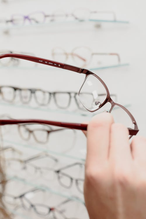 Crop anonymous female buyer making choice of rim in optical store with various eyeglasses