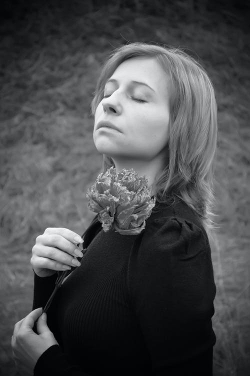 Side view of black and white of romantic young female with flower in hand relaxing in nature with closed eyes on cloudy day