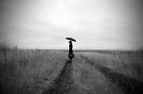 Anonymous elegant woman with umbrella standing on dry field on overcast autumn day