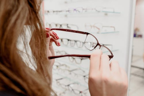 Woman selecting eyewear in store with various rims